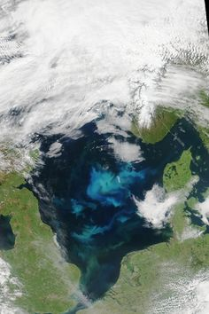 Bloom of greenish blue phytoplankton in dark blue waters with clouds overhead