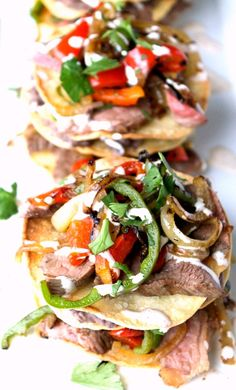 Steak Fajita Tostada Stacks have grilled steak, onions, peppers and creamy refried black beans layered between lime flavored tostada shells. Mexican Crema, Steak Fajitas, Corn Tortillas, Refried Beans, Tostadas, Veggies, Cocktails, Stuffed Peppers, Baking