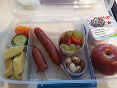 Chorizo sausages, avocado, cucumber and carrot coins, mixed nuts, yogurt, strawberries, grapes and an apple.