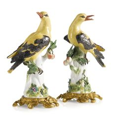 A PAIR OF MEISSEN PORCELAIN ORMOLU-MOUNTED FIGURES OF GOLDEN ORIOLES THE PORCELAIN CIRCA 1750, THE ORMOLU LATER each brightly colored bird modelled perched on the leafy stump of a cherry tree and mounted on an ormolu foliate scrollwork base, crossed swords marks in underglaze-blue.   height of porcelain 10 1/8 in.; height overall 11 3/8 in. 25.7 cm; 28.9 cm