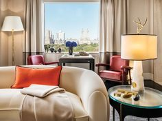 The view of Central Park takes center stage, accented by red leather lounge chairs by Jacques Adnet (1950), and an ebony games table. On the FontanaArte side table, a Nemo table lamp from the Achille Salvagni Atelier collection, in onyx and bronze.