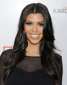 Browse the best Kardashian Jenner hair moments for inspiration    Kourtney Kardashian's middle part and loose curls