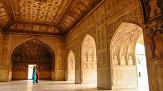 Two women walk in the ornate Agra Fort.