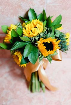 Brides.com: . Sunflower. Big and lush, sunflowers — symbolic of dedicated love — are beloved for their striking appearance and look-at-me allure and are often used at rustic, country-themed nuptials.