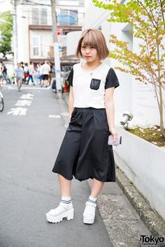 Saki on the street in Harajuku wearing a black and white look featuring Nadia wide leg pants and platform sandals with socks.