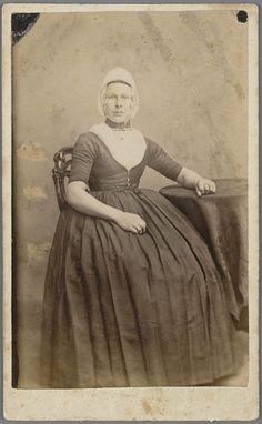 Vrouw in Walcherse streekdracht. De vrouw is gekleed in zondagse dracht of uitgaansdracht. Onder de 'trekmuts' word een ondermuts gedragen, waarin het oorijzer is gespeld. Aan de uiteinden van het oorijzer bevinden zich gouden windingen, de 'krullen'. Aan de krullen hangen klaverbladvormige oorijzerhangers. Om haar hals draagt ze een halssnoer. In de uitsnijding van het jak is de beuk (kroplap) zichtbaar. Om de vingers wordt een aantal ringen gedragen. 1875-1890 #Zeeland #Walcheren