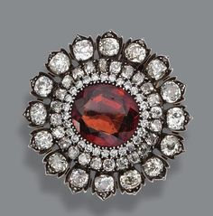 GARNET AND DIAMOND BROOCH, CIRCA 1880 The floral medallion set in the center with a cushion-shaped garnet encircled by 40 old-mine and 28 round diamonds weighing a total of approximately 10.50 carats, mounted in silver and gold, clip signed Bulgari.