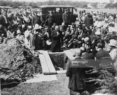 Photo shows ceremonies being enacted about the grave of Celestine Madeiros, slayer of a Wrentham Bank cashier who was executed with Sacco and Vanzetti. Madeiros' casket may be seen in the grave.