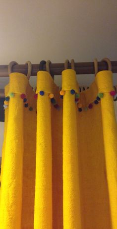 Yellow wool curtains with a pom pom trimming