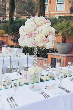 Cut crystal topiary bases upped the glamorous feel and held high centerpieces of white and ivory hydrangea dotted with baby pink and blush roses.  Cresol candle holders, rose petals, and votives gave a soft, romantic feel.  Las Vegas Wedding Planner Andrea Eppolito  |  Wedding at Lake Las Vegas  | White and Blush and Grey Wedding
