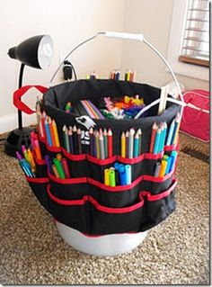 Buy a Bucket Boss (a portable tool belt that hooks on a bucket) from a building supply store for about $7, put it on a bucket, and add the kids' art supplies & small games. Inside holds big stuff like paper and all the pockets on the outside are for pens, markers, glue, scissors, small games, etc.-- need to do this for the kids for xmas!
