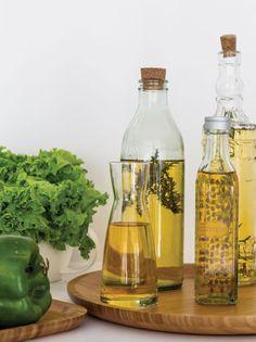Una buena colección de botellas de vidrio llenas de aceite de oliva y hierbas puede agregar calidez a la decoración de la cocina.