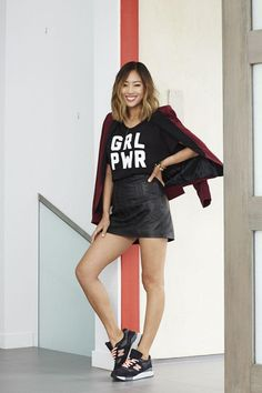 "How to Style Your Sneakers in Summer - ""GRL PWR"" graphic t-shirt, over-the-shoulder blazer, an edgy leather mini skirt, + black and peach New Balance sneakers"