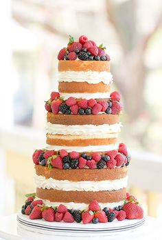 A three-tiered naked vanilla cake filled with frosting and topped with fresh strawberries, raspberries, blueberries, and blackberries, created by The Sugar Suite.