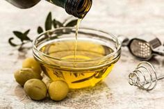 Olive oil health benefits-a bowl of olive oil with green olives nearby Omega Fettsäuren, Olive Oil Benefits, Keto Vegan, Home Remedies For Hair, Cooking Oil, Camping Cooking, Oven Cooking, Cooking Games, Cooking Turkey