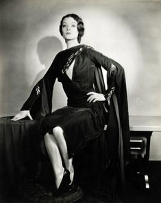 Myrna Loy 1930s photo print ad model movie star flowing draping dress wide bell sleeves dramatic unique designer gown dress embroidered leaves floral shoes hair black
