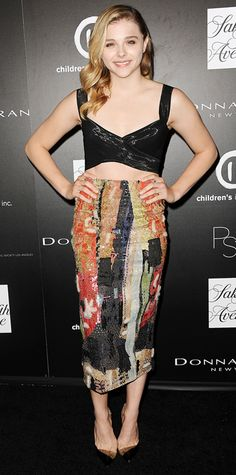 Chloe Grace Moretz revealed a sliver of midriff at the PSLA Autumn Party in a black bustier top and a colorful shin-grazing pencil skirt, both by Donna Karan, and black PVC Louboutin pumps.
