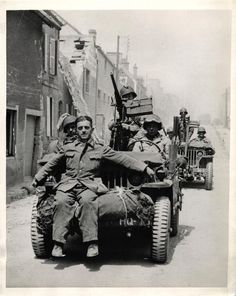 1944 - German sniper, captured in St. Mere Eglise, rides off to captivity on the front bumper of a jeep.