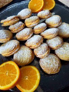 Για την ζύμη: 1&12 φλιτζάνι φαρίνα 220 γρ. Βούτυρο 12 φλιτζάνι άχνη ζάχαρη 1κ.σ. κορν φλαουρ 2κ.σ. ξύσμα πορτοκαλιού Για την γέμιση: 60γρ. Βούτυρο 1 φλιτζάνι άχνη ζάχαρη 3κ.σ. χυμό πορτοκαλιού 1 βανίλια 2 σταγόνες Χρώμα ζαχαροπλαστικής πορτοκάλι. Εκτέλεση: Χτυπάς το βούτυρο με την άχνη και το ξύσμα