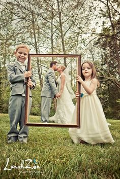 A Love-ly work of art! Ring-bearer and flower girl hold up a frame to frame the bride and groom.