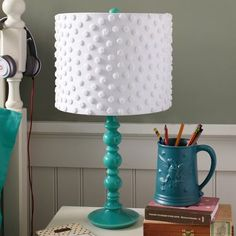 get the same look of this 50 dollar pottery barn lampshade by gluing white pom poms on a white drum shade. This is perfect for the baby's room I even have the turquoise base.