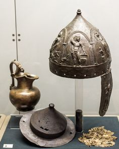 Burial of a Thracian auxiliary soldier (Eftatralis?) from Kara Agach/Bryastovets 11 | by diffendale. Bronze helmet (inv. no. 6176), bronze shield boss, bronze scales from a cuirass (so-called lorica squamata), and a bronze trefoil pitcher. The burial, attributed to a Roman auxiliary soldier (whether archer or cavalryman is debated), is dated to the late 1st c. CE. Not displayed: several other bronze vessels, a bronze lantern, and fragments of iron swords and spearheads from the burial.