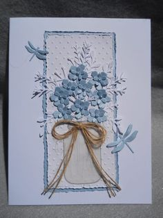 Blue flowers in mason jar, lacy foliage, blue dragon flies, lacy bouquet in blue Heavy ivory card stock Swiss dot embossing folder Swiss dot background edged with blue and frayed edging on both Two blue dragonfly dance around the bouquet Blue flowers all have pearl centers~ photo is a low