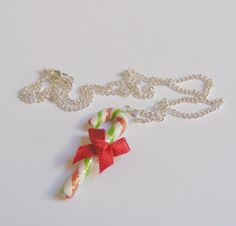 From the silver plated chain (which is lead, cadmium and nickel free) hangs the cutest little sparkly, green, red and white striped candy cane, tied