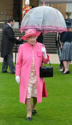 Britain's Queen Elizabeth II walks under an umbrella in the garden of Buckingham Palace in London as up to 8,000 guests attend the first royal garden party of the year on May 10, 2016.