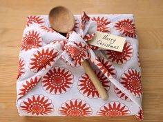 Tea Towel Tie a charming teal towel around a cookbook to create wrap that's also part of the gift. Weave in a wooden spoon to sweeten the deal even more.