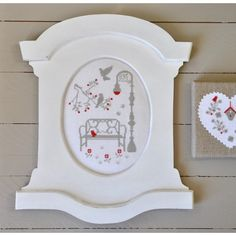 This site offers the frame for sale, no chart for the cross stitch. I like the idea of using red as an accent color, and the finish on the right: looks like linen stretched over canvas or a frame and then the cross stitch on top. Cute!