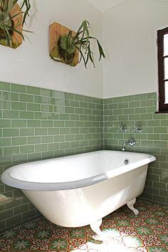 A Sofia cement tile floor plus green tiled walls plus Staghorn ferns equal zen calm.