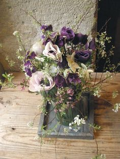 Unstructured wildflower style arrangement in purples and creams with anemones and blossom -Frederic Garrigues