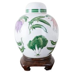 Charming Chinese export porcelain lidded ginger jar on a hardwood stand. Features a highly decorated round form with colorful vegetables over a white ground. The vase with its round lid measures 10 inches high without its stand.