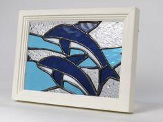 イルカをモチーフにしたステンドグラスパネルを市販の額縁に入れました。スタンド(丸棒 取り外し可)と裏面に壁掛け金具が付いていますので、棚置きでも壁掛けでも飾ることが出来ます。*材質:ガラス、カッパ(銅)テープ、*額縁(木製 オフホワイト色) *脱着式金属...