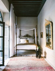 vintage moroccan berber rug in bedroom with tall ceilings and four post bed. / sfgirlbybay