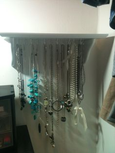 Measure and mark dots 1-2 apart on the bottom of a shelf.  Drill holes.  Screw in cup hooks.  Hang Necklaces! catline1