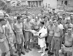 Commander Peter MacRitchie of H.M.C.S. PRINCE ROBERT meeting with liberated Canadian prisoners-of-war at Sham Shui Po Camp, Kowloon, Hong Kong, via Flickr.