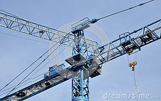 Blue tower cranes on a building site under blue sky