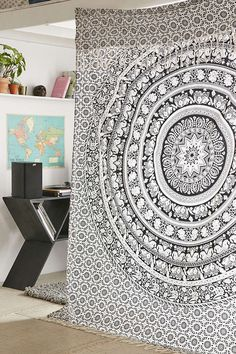 Giant flat sheet or tapestry as room divider? Genius!  (Oh and I'm loving that end table, and the floating shelf mantle)!!
