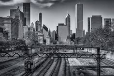 The Metra Electric and South Shore Line tracks pass through Chicago's Grant Park as the city's skyline rises in the distance. #chicago #skylines #cityscapes #blackandwhite See more photos at 75central.com
