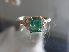 14kt yellow gold cluster style setting with 7x5 emerald cut emerald center