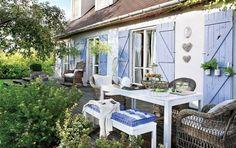 niebieskie okiennice w białym domku  z pięknym drewnianym tarasem