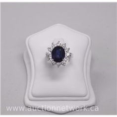 Ladies 18kt White Gold Diamond and Sapphire Ring with 1 Oval Faceted Cut Sapphire (6.10ct) and 12 Ro - Auction Network