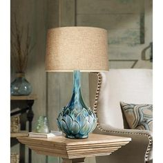 Featuring a textured petal detail near the bottom of the base, this stunning ceramic table lamp is topped with a linen drum shade.