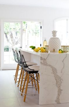 White kitchen with Calcutta marble island bench ceramic pineapple jar drink dispenser and french wooden doors