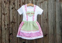 Mit dem #Kinderdirndl in rosa mir Rosen ist Dein Mädchen schick und bequem angezogen. Bei Familienfeier, Hochzeit oder anderer Festlichkeit werdet Ihr viele bewundernde Blicke auf Euch ziehen.  Der Rock ist aus rosa Baumwollstoff, der mit Rosen bedruckt ist und einer Wäschespitze genäht, die Schürze ist aus grün-weißemund pink-weißem Baumwollstoff gefertigt auf den ein rosa Satinband und eine Herzborte genäht ist. Beim Bund des Röckchens sorgt die Einarbeitung eines Gummis für noch mehr…