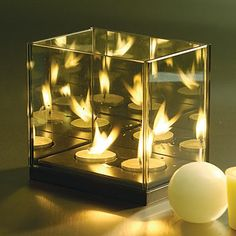 Infinity Glass Double Tea Light Holder - SKU2478 $26.00 The unique design of this 2 tealight holder appears to light the way to infinity. Subtly smoked glass mirrors reflect against each other when the tealights are lit, providing a seemingly endless display of lights. This piece is a beautiful and mystifying addition to any decor. Sits on a black wooden base. 2 Tea lights included. 5.5x4x5