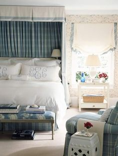 Deliciously cozy blue and white master bedroom in a country house by Ashley Whittaker. Love the mixing of florals and plaids, and a perfect canopy with white fabric and satin ribbon trim on the outside and blue and white plaid on the inside. Petite pleated swing arm sconces inside the canopy are a favorite. Gorgeous monogrammed linens, garden stool, skirted armchair, and lovely bench at the foot of the bed complete the look. Very old school ideas, yet totally fresh.