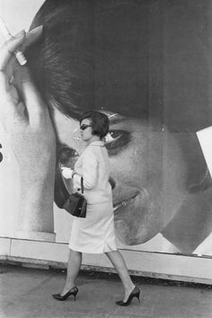 "William Gedney. ""Woman in high heels walking by a large billboard of a woman smoking"". 1966. San Francisco, CA, USA."